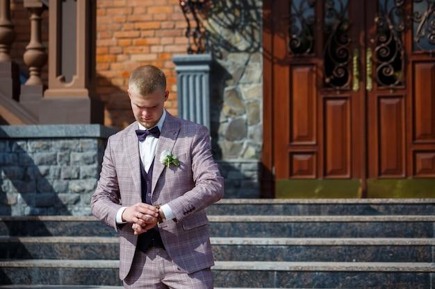 Жених в красивом клетчатом костюме и галстуке-бабочке