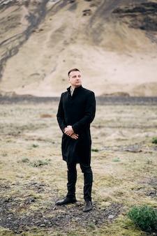 Жених в черном пальто на фоне горы. свадьба в исландии.