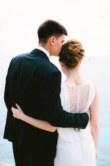 Жених в черном костюме обнимает и целует невесту в белом красивом кружевном платье в храме, вид сзади