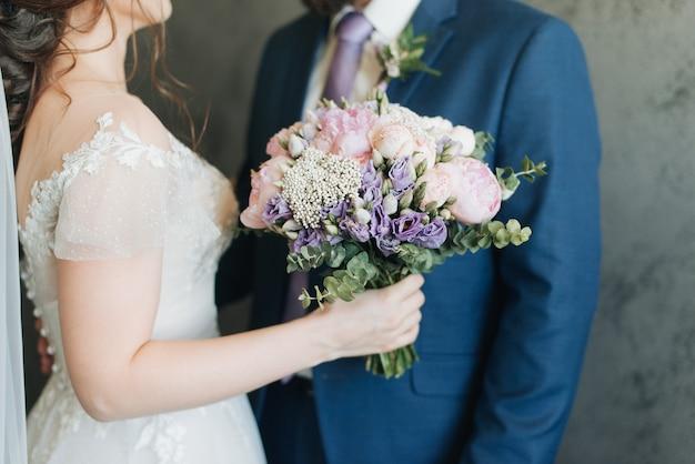 青いジャケットを着た新郎と花束を手にした花嫁の結婚式の日