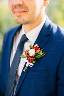 青いジャケットのネクタイと白いシャツを着た新郎と襟にブートニエール