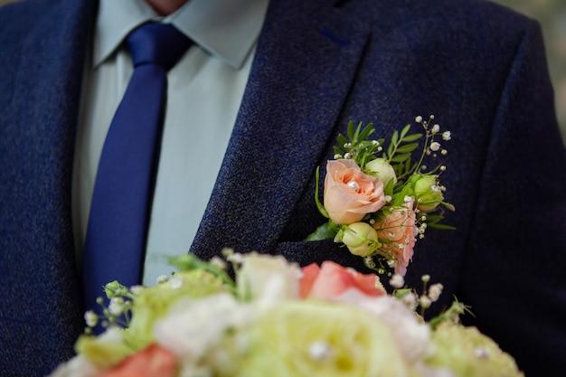 青いスーツとネクタイで新郎。結婚式の日。ブートニア、ブーケ。ボケ
