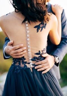 青いスーツを着た新郎は、腰のクローズアップの背面図で青いドレスを着た花嫁を抱きしめます