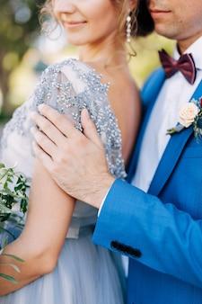 Жених в синем костюме обнимает невесту с букетом цветов за плечи крупным планом