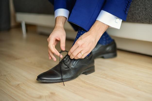 Жених в синем костюме завязывает шнурки