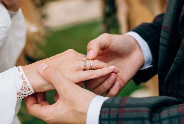 Жених в клетчатом костюме кладет кольцо на руку невесты крупным планом