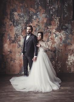 スーツを着た新郎とウェディングドレスを着た花嫁。彼らの結婚式の日に若いカップルを叩きます