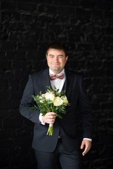 Жених в костюме держит свадебный букет