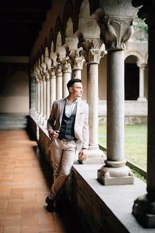 スーツを着た新郎が古い建物の柱状のロッジアの上に立っている