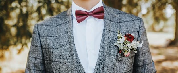 自然の中で結婚式の花のブートニアと赤い蝶ネクタイとスーツの新郎