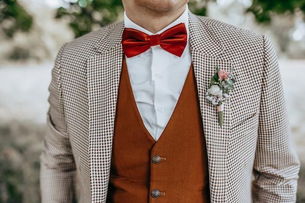 Жених в костюме со свадебной цветочной бутоньеркой и красным галстуком-бабочкой на природе