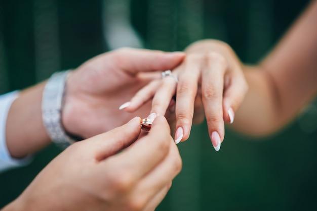 시계와 양복을 입은 신랑은 신부의 손가락에 결혼 반지를 댄다.