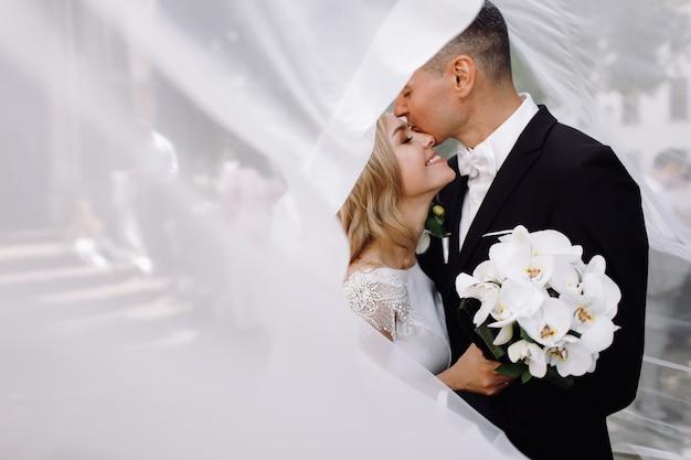 Жених в черном смокинге обнимает нежную потрясающую невесту, пока они стоят