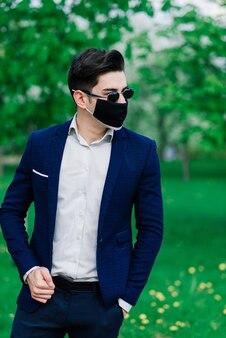 屋外の公園での結婚式の前に、医療用マスクで新郎をします。