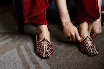 Groom in red velvet trousers puts on golden wedding shoes