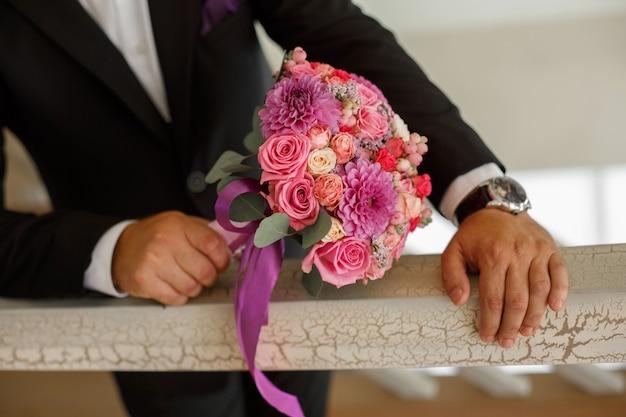 スーツの新郎は花嫁のためのウェディングブーケを保持します。花とロマンチックなデートの準備をしている人がクローズアップ