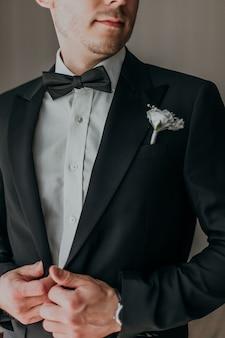 ホテルのホールで笑顔で花嫁を待っている結婚式の黒タキシードの新郎。衣装と蝶ネクタイのエレガントな新郎。