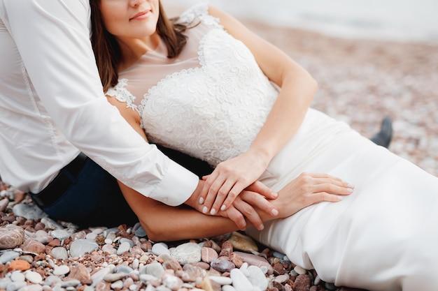 Жених в белой рубашке обнимает невесту, лежащую в белом кружевном платье