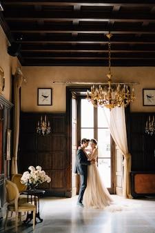 신랑은 오래된 빌라에서 장미 꽃다발과 함께 테이블 맞은 편 방에서 신부와 함께 춤을 추고 있습니다.