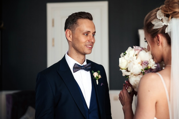 Groom is looking at his beautiful bride