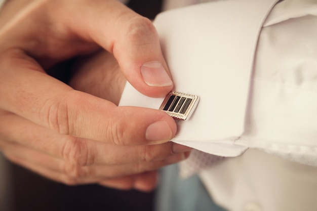 Groom is putting on cuff-links as he gets dressed in formal wear close up