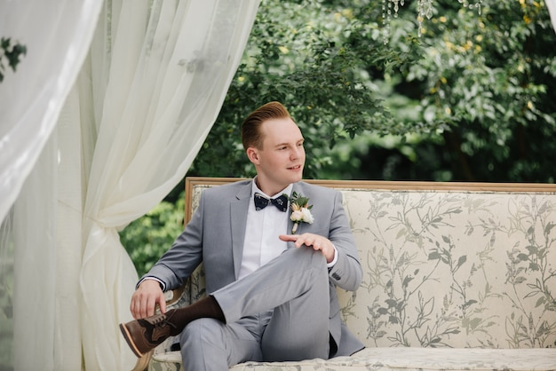 The groom is sitting on a beautiful couch in a gazebo in the garden. white tent. green foliage. the bride in a pink fluffy dress, the groom in a gray suit.