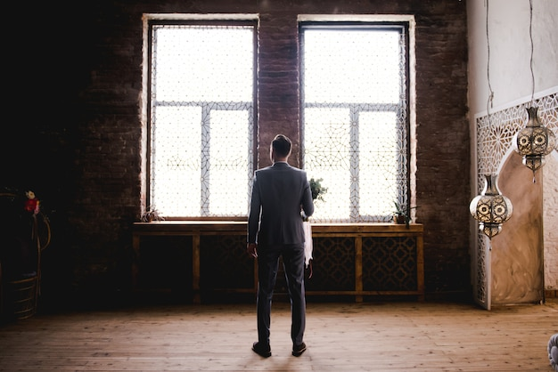 The groom is waiting for the bride in a gray suit.
