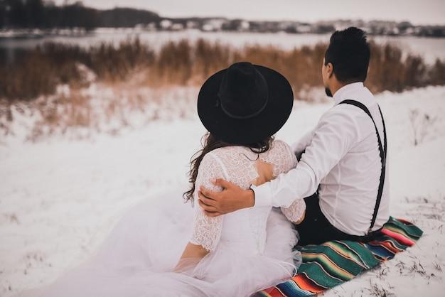 雪に覆われた丘の上のメキシコの国民のベールで花嫁とその手入れをする