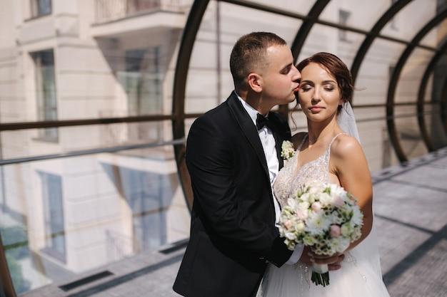 Groom kiss and hug his wife. bride in elegant wedding dress.