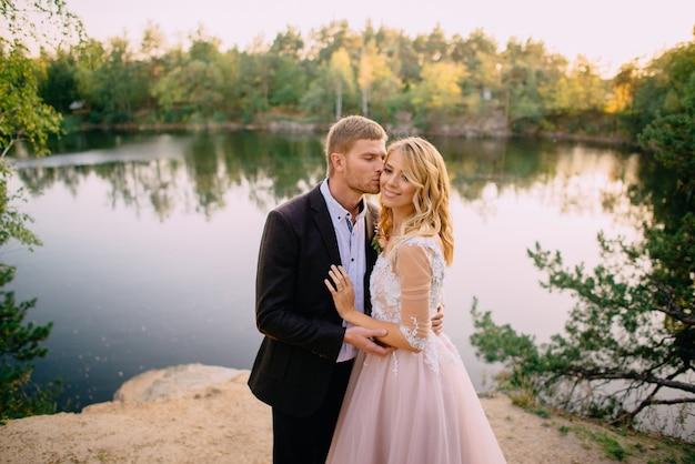 新郎は日没時に自然を背景に幸せな花嫁にキスします