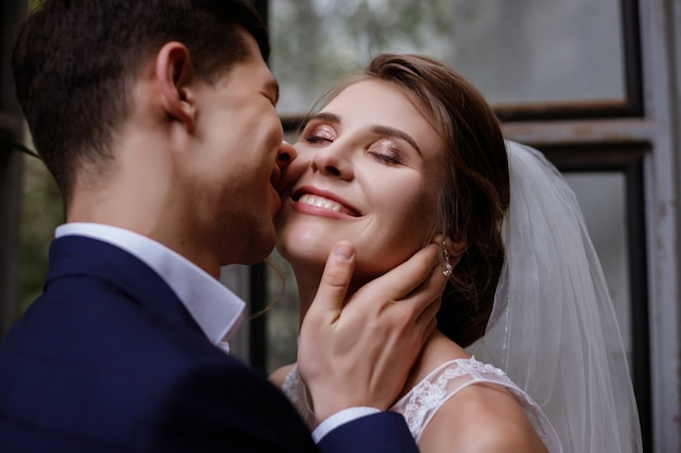 Groom kisses the bride on the cheek. the bride is happy
