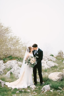 Groom kisses bride in a long dress with a veil and a bouquet of flowers on the background of rocks