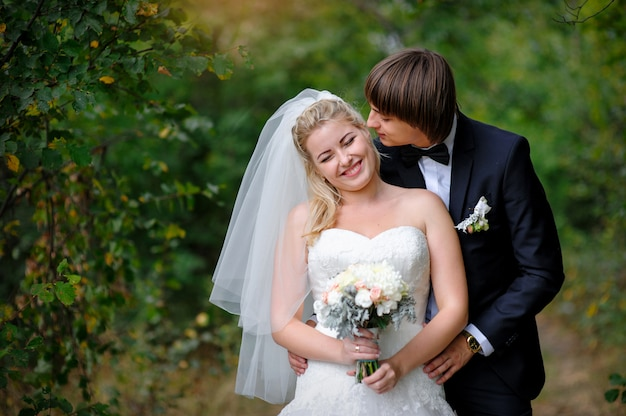 Groom kisses the bride in love in the summer park