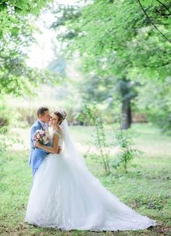 Groom kisses bride's cheek tender standing with her in green park