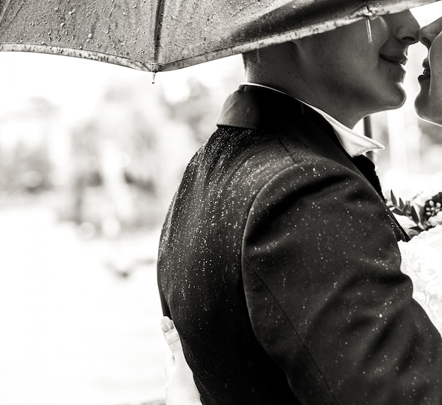 Groom kisses bride's tender standing under umbrella in the rain