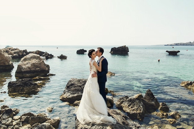 Groom kisses bride tender on the rocks over ocean