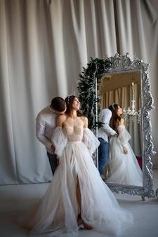 Жених целует невесту в свадебном платье