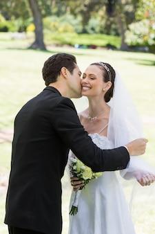 Groom kissing bride in garden