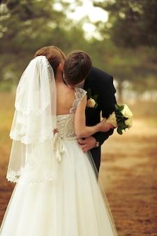 森で花嫁にキスする新郎