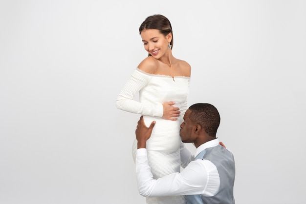 Groom kissing his pregnant bride's belly