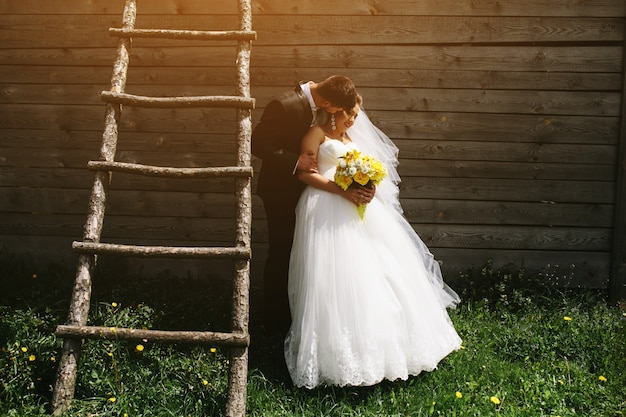 Groom kissing his wife next to a hut