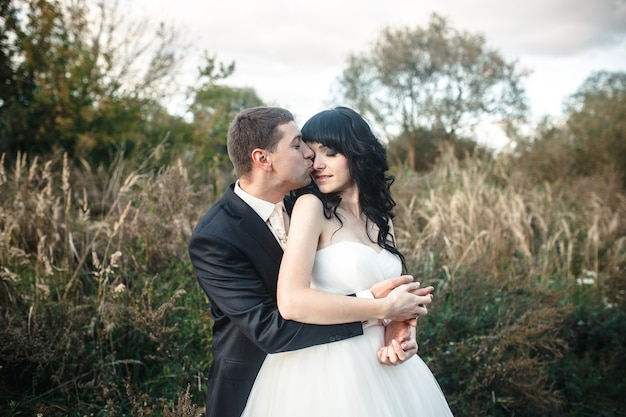 Groom kissing his wife outdoors