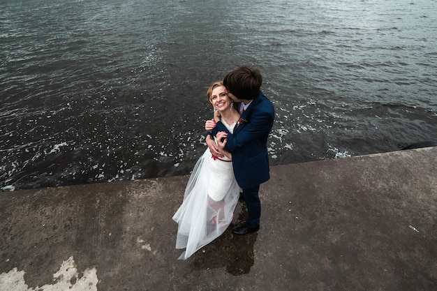 Groom kissing his wife's cheek by the lake