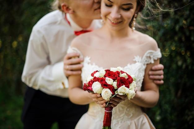 緑の木の背景に結婚式の花束を持っている彼の若くて美しい花嫁にキスする新郎