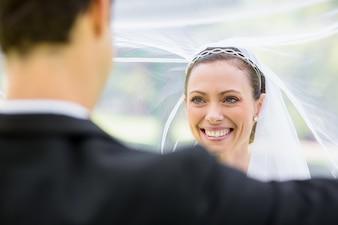 Groom lifting bridal veil