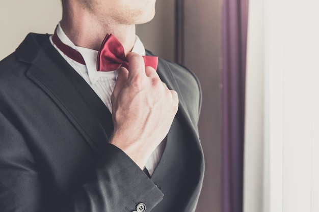 Groom looking in mirror and touching bowtie