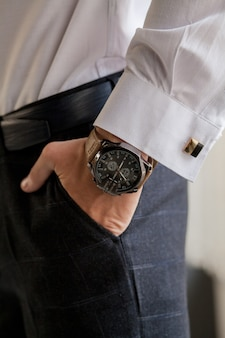 The groom looks at his watch to check the time. the watch is worn on the man's hand. groom's morning preparation before wedding