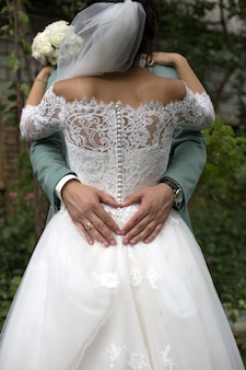 The groom makes the heart with his hands on the dress of the bride. newlyweds hugging