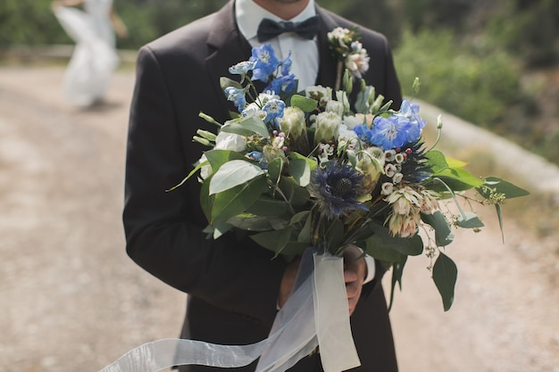 Groom meets the bride with a bouquet of flowers