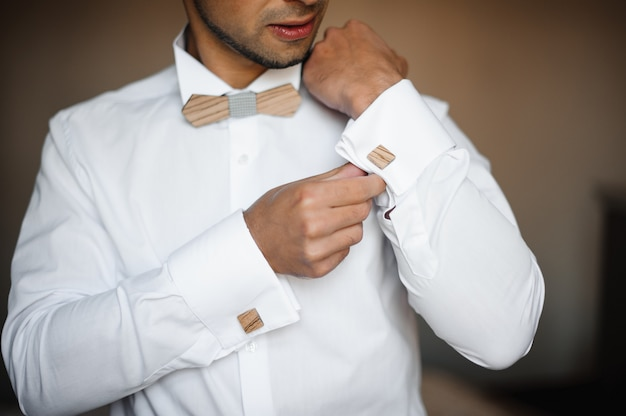 Groom morning preparation. young bearded groom getting dressed in wedding shirt with wooden bow tie